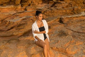 Model wearing Australian Pearls and white shirt sitting on Broome rocks. This page tells you how to care for your pearls
